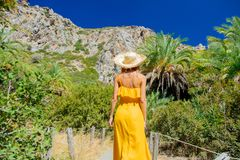 Girl have rest in palm forest. Young girl in yellow dress and hat have rest in palm forest of Preveli, Crete, Greece royalty free stock photography