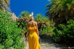 Girl have rest in palm forest. Young girl in yellow dress and hat have rest in palm forest of Preveli, Crete, Greece royalty free stock images