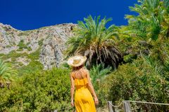 Girl have rest in palm forest. Young girl in yellow dress and hat have rest in palm forest of Preveli, Crete, Greece stock photos
