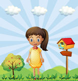A young girl with a yellow dress standing near the pethouse Royalty Free Stock Photo