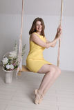 Young girl in yellow dress on swing in a room Stock Photo