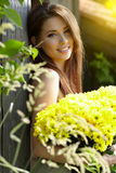 Young girl with yellow flowers Stock Images