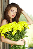 Young girl with yellow flowers Stock Image