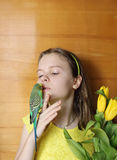 Young girl with yellow flowers and green bird (little parrot) Royalty Free Stock Photo