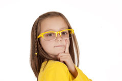 Young girl in yellow glasses posing with finger on cheek Stock Image
