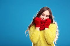 Young girl in yellow sweater, red gloves. Beautiful young girl in yellow sweater, red gloves and scarf on blue background stock photography