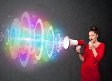 Young girl yells into a loudspeaker and colorful energy beam com Stock Image