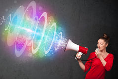 Young girl yells into a loudspeaker and colorful energy beam com Royalty Free Stock Photos
