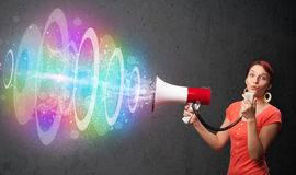 Young girl yells into a loudspeaker and colorful energy beam com Royalty Free Stock Photography