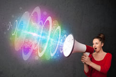 Young girl yells into a loudspeaker and colorful energy beam com Stock Photography