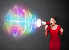 Young girl yells into a loudspeaker and colorful energy beam com Royalty Free Stock Images