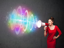 Young girl yells into a loudspeaker and colorful energy beam com Stock Photos