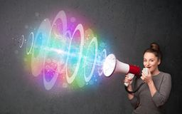 Young girl yells into a loudspeaker and colorful energy beam com Royalty Free Stock Image