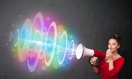 Young girl yells into a loudspeaker and colorful energy beam com Stock Photo
