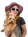 Young girl with a yorkshire terrier. Young girl with sunglasses and hat, holding a yorkshire terrier dog Royalty Free Stock Photos