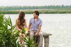 Young girl and the young man on the dock by the river. Girl and the young men on the dock by the river royalty free stock photo