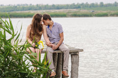 Young girl and the young man on the dock by the river Stock Photos