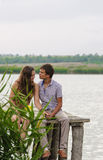 Young girl and the young man on the dock by the river Stock Photography