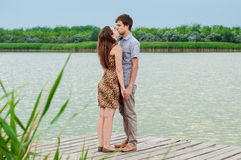 Young girl and the young man on the dock by the river Stock Image