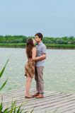 Young girl and the young man on the dock by the river. Girl and the young men on the dock by the river royalty free stock image