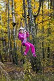 Girl on Zip Line. Young girl on zip line between trees in an adventure park stock photography