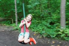 Young Girl on Zip Wire. Panned Photograph of Young Girl on Zip Wire with Motion-Blurred Background Stock Photo
