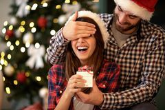 Girlfriend and boyfriend celebrating Christmas. Young girlfriend and boyfriend celebrating Christmas royalty free stock image
