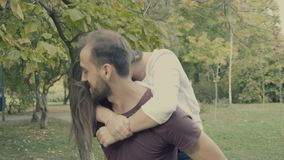 Young girlfriend jumps in her boyfriend arms. In the park. Slow motion 4K footage with cinematic color grading stock footage