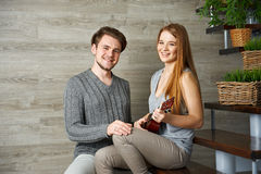 Young girlfriend playing ukulele for her boyfriend Stock Photos