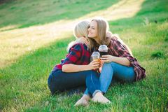 Two young women sitting on grass hugging. royalty free stock photo