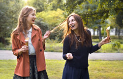 Young girlfriends laughing with ice cream. Two young girlfriends laughing with ice cream Stock Image