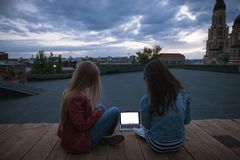 Young girlfriends are looking at a white laptop Royalty Free Stock Images