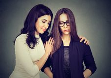 Young girlfriends overcoming troubles together. Woman consoling young sad friend helping to cope with problems royalty free stock photography