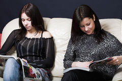 Young girlfriends reading magazine Stock Images