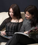 Young girlfriends reading magazine Royalty Free Stock Image