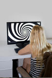 Young girlis looking at hypnosis spiral on her computer. Young girl with long blond hair is looking at hypnosis spiral on her computer stock photos