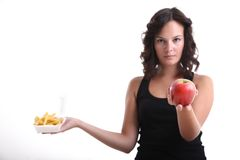 Young girls with an apple and french fries. Young girls offer an apple and take off french fries Royalty Free Stock Photography