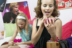 Young Girls Applying Makeup In Bedroom Stock Image