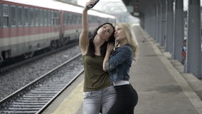 Young girls arriving and meeting in train station and taking a selfie pictures with smartphone. Excited young girls arriving and meeting in train station and stock video
