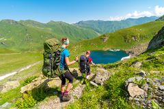 Young girls backpacking towards a lake in Greater Caucasus mount. Ains on a sunny day, Mestia district, Svaneti, Georgia stock photo