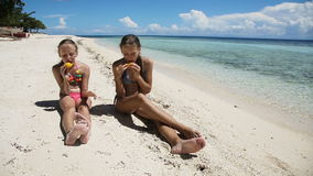 Young girls on the beach eating mango fruit. Two girl sisters sitting on a tropical beach,eat mango.children eats mango on the shore of tropical sea on a white stock footage