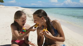 Young girls on the beach eating mango fruit. Two girl sisters sitting on a tropical beach,eat mango.children eats mango on the shore of tropical sea on a white stock video