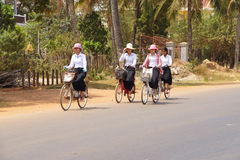 Young girls bicycle home from school Royalty Free Stock Images
