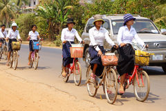 Young girls bicycle home from school Stock Photos