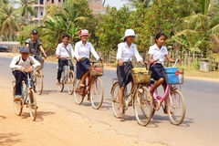 Young girls bicycle home from school Royalty Free Stock Photography
