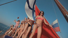 Young girls in bikini relaxing on a yacht with red stock video