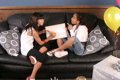Young girls birthday party fun. Two young girls have fun and laughter at a birthday partydrawing on a dry erase board with a giant pencilblank for your text royalty free stock photography