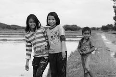Young girls and a boy of countryside paddy field get muddy after catching mussels. Young girls and a boy walking along countryside farming fields searching to Stock Images