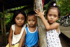 Young girls and boy looking at the camera in Aklan province in the Philippines. royalty free stock photography