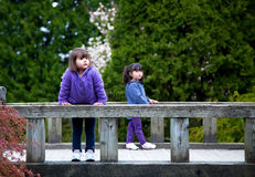 Young girls on a bridge enjoying nature. Young sisters stop on a bridge in the park to rest and enjoy the view Royalty Free Stock Photo